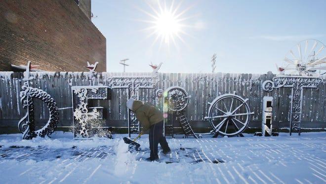 Joshua Wade, 19, of Detroit, shovels his uncle Carlos Nielbock's sidewalk in front of some of Nielbock's welded artwork at 2264 Wilkins Street in Detroit Sunday, Nov. 22, 2015.