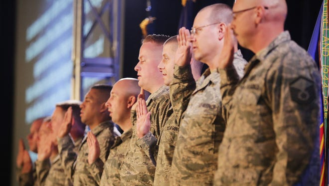 Gov. Rick Snyder leads the Air National Guardsmen in their Oath of Reenlistment during the 127th Wing Welcome Home Ceremony at Selfridge Air National Guard Base in Harrison Township, Sunday, Dec. 6, 2015.