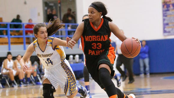 Morgan Park's Deja Cage pushes the ball up court covered