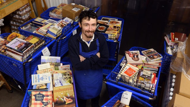 Joe Gonzales, manager of St. Vincent de Paul, poses with shopping carts full of cookbooks that will be on sale Monday.
