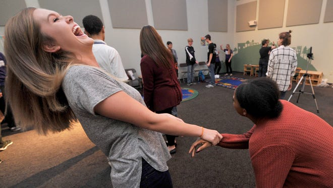 Camille Lecrone, left, can't stop laughing as she takes a self-defense session with fellow Spring Grove junior Kiana Graham during the Youth Empowerment Summit at Martin Library.