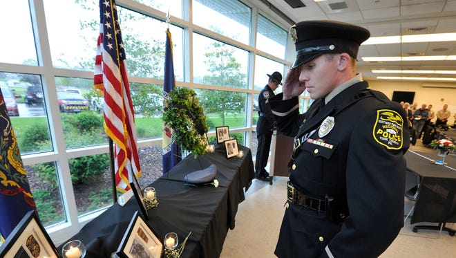 Officer Lynn Anderson with the Northern Regional Police Department places a carnation and pays his respect to fallen officers during the annual police memorial service.