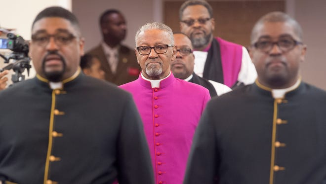 Led in by his sons, Carl Shannon Scott, left, and Shelton Scott, Carl H. Scott  processes in during his sacred service to become Bishop at the Bible Tabernacle Christian Center.