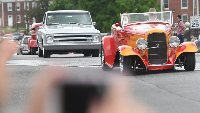 People take photos as street rods participate in the Street Rod Nationals East parade along Market Street on Friday, June 3, 2016.