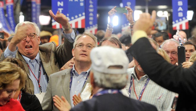 David Johnson, left, a delegate from Ohio reacts to Pennsylvania delegates Joe Sacco, center, and Matthew Jansen, after they gave the Ohio delegates a thumbs down for casting their votes for Gov. John Kasich during the Republican National Convention held at the Quicken Loans Arena on Tuesday, July 19, 2016.