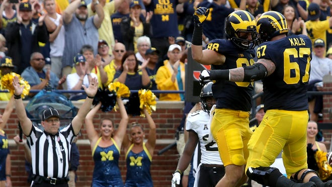 Michigan tight end Jake Butt and teammate #67 Kyle Kalis celebrate Butt's TD against Central Florida at Michigan Stadium on Saturday, Sept.10, 2016.
