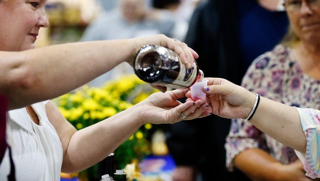Naylor Wine Cellars employee Wendy Rommel, left, pours a sample Saturday at the 19th annual Women's Show at the York Expo Center in West Manchester Township.