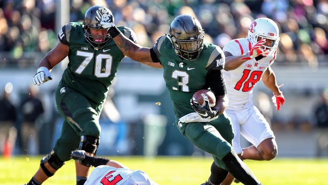 LJ Scott (3) runs in front of a Tyler Higby block during Michigan State's 49-0 win over Rutgers last season.