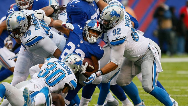 Dec 18, 2016; East Rutherford, NJ, USA;  Giants running back Rashad Jennings is tackled by Lions defensive tackle Haloti Ngata (92) and defensive back Asa Jackson (30) during first half at MetLife Stadium.