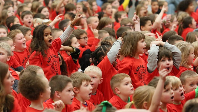 "Coshocton Elementary first-grader Kinlee Carroll, top left, holds up her finger while singing ""This Little Light of Mine,"" Tuesday, with the rest of the students while wearing ""I am a LIGHT"" shirts, denoting Leader, Imaginative, Giving, Helpful, Trustworthy. Fifth- and sixth-grade students performed for their entire school singing songs from various holidays celebrated in December."