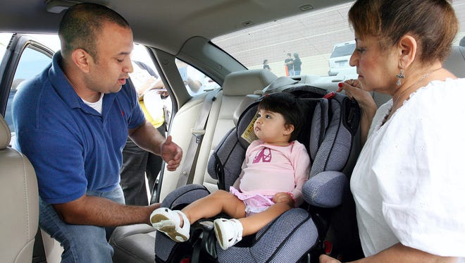 Mark Flores (left) inspects the safety car seat in the back seat of Esther Castaneda's (right) car in a past car seat inspection in Corpus Christi.