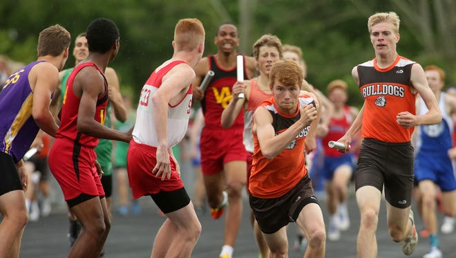 Heath senior Taylor Hopkins prepares to pass the baton to junior Nick Lee in the 4x800 Thursday during the Division II regional track meet.