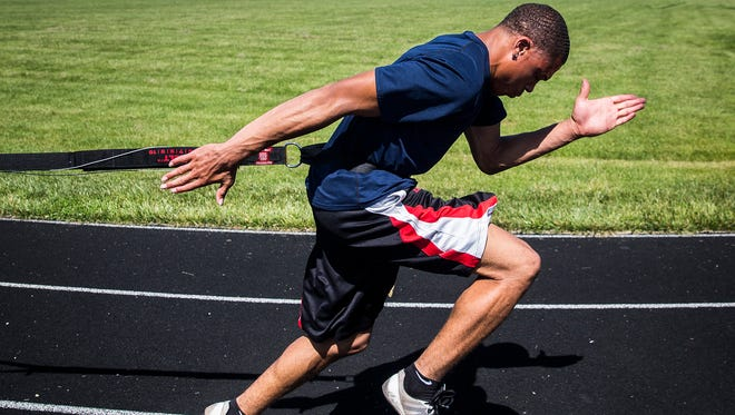 Central's Eliseus Young does resistance training off of the block with coach Jason Wray while preparing for state at Central Thursday, June 1, 2017.