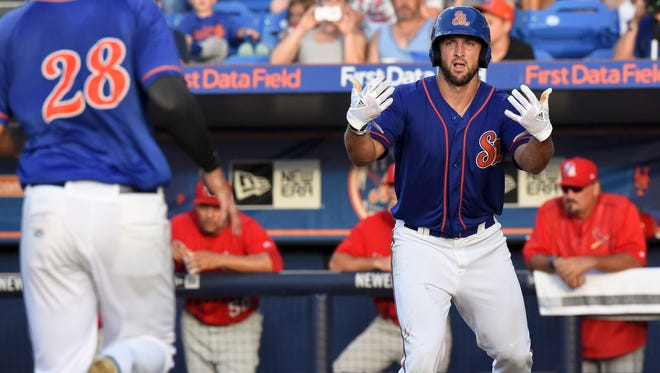 St. Lucie Mets left fielder Tim Tebow waves in teammate Wuilmer Becerra on Thursday, June 29, 2017, after scoring a run during their game against the Palm Beach Cardinals at First Data Field in Port St. Lucie. To see more photos, go to TCPalm.com.