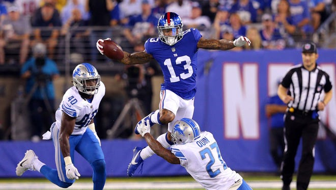 Sep 18, 2017; East Rutherford, NJ, USA; Giants receiver Odell Beckham Jr. is tripped up by Lions safety Glover Quin, as linebacker Jarrad Davis pursues in the second quarter at MetLife Stadium.