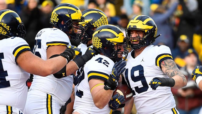 Michigan's Henry Poggi (19) is congratulated by Ben Mason (42) and more teammates after scoring a touchdown against Maryland last season.
