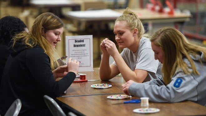 St. Cloud State students assemble beaded bracelets that will be given to Ngatha International, an organization that provides support to children in Africa, following the Martin Luther King Jr. Breakfast Monday, Jan. 15, at Halenbeck Hall in St. Cloud.