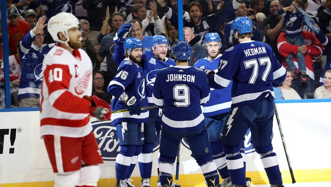 The Lightning celebrate a goal against the Red Wings, as Henrik Zetterberg skates past during the first period at Amalie Arena on Thursday.