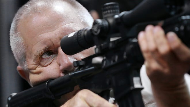 Dennis Wolken of Paxton, Ill., checks out a sight  during the NRA Convention in Indianapolis on April 25, 2014.
