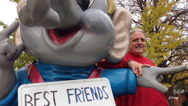 Stewart Moyer, 68, of Farmington Hills poses with Izzy the elephant at his home on Thursday.