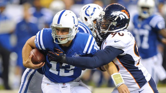 Indianapolis Colts' Andrew Luck (12) is brought down in the backfield by Denver Broncos' Shaun Phillips (90) during the first half of Sunday night's game at Lucas Oil Stadium on October 20, 2013. Matt Detrich / The Star