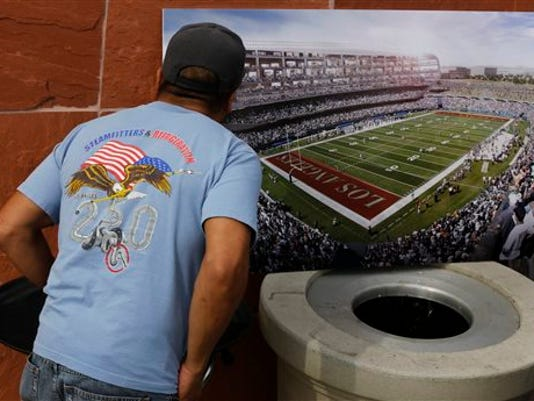 FILE - In this Feb. 19, 2015, file photo, a football fan checks a rendering for a proposed NFL football stadium by the owners of the San Diego Chargers and Oakland Raiders during a news conference in Carson, Calif.