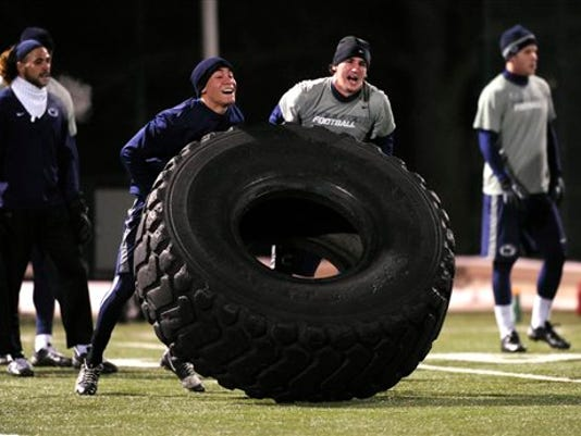 Penn State football players flip tires as part of their workout during a Penn State University football team strength and conditioning practice on Friday, Feb. 8, 2013, on the campus, in State College, Pa. (AP Photo/Centre Daily Times, Nabil K. Mark)