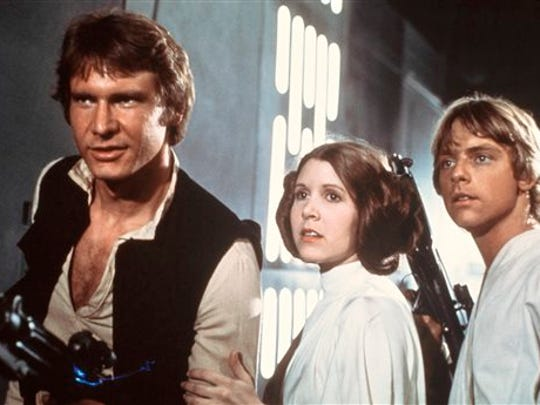 """In this 1977 image provided by 20th Century-Fox Film Corporation, from left, Harrison Ford, Carrie Fisher, and Mark Hamill are shown in a scene from """"Star Wars"""" movie released by 20th Century-Fox.  From the set of """"Star Wars: Episode VII"""" in Abu Dhabi, director J.J. Abrams announced the launch of Star Wars: Force for Change, a campaign to raise funds for United Nations Children's Fund's (UNICEF).  The campaign will run from 12:01 a.m. PDT on May 21, 2014, until 11:59 p.m. PDT on July 18. (AP Photo/20th Century-Fox Film Corporation)"""