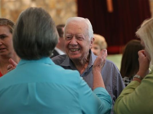 FILE- In this Sunday, Aug. 16, 2015, file photo, former President Jimmy Carter reaches to embrace his brother Billy's widow Sybil while greeting family following service at Maranatha Baptist Church in Plains, Ga. Carter's nieces Mandy Flynn, left, and Jana Carter are also pictured. Jimmy Carter plans to discuss his recent cancer diagnosis Thursday, Aug. 20, for the first time since revealing last week that he was ill.