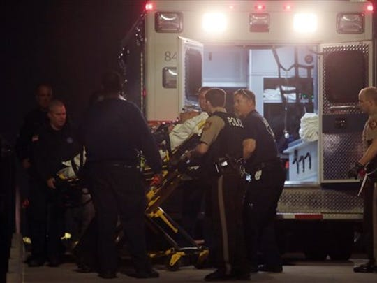 Paramedics load one of two police officers who were shot while standing guard in front of the Ferguson Police Station during a protest on Thursday, March 12, 2015. A 32-year-old officer from nearby Webster Groves was shot in the face and a 41-year-old officer from St. Louis County was shot in the shoulder, St. Louis County Police Chief Jon Belmar said at a news conference. Both were taken to a hospital, where Belmar said they were conscious. (AP Photo/St. Louis Post-Dispatch, Laurie Skrivan) EDWARDSVILLE INTELLIGENCER OUT; THE ALTON TELEGRAPH OUT