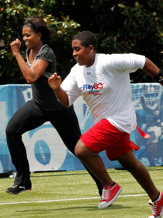 FILE - In this Sept. 8, 2010, file photo, First lady Michelle Obama runs a 40-yard sprint as she participates in the Let's Move! Campaign and the NFL's Play 60 Campaign festivities with area youth, to promote exercise and fight childhood obesity, in New Orleans. When the NFL launched Play 60 a decade ago as a way to get American youth active, the league had no idea what kind of reach the program would have. Ten years later, millions of youngsters and 73,000 schools have become involved, and affiliations with such organizations as the American Heart Association and the National Dairy Council have helpoed make Play 60 one of the nation's most effective anti-obesity and children's activity initiatives in the land. (AP Photo/Gerald Herbert, File)