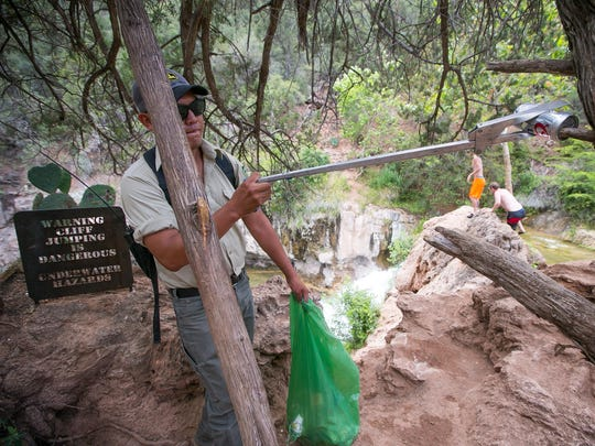 Forestry technician Jeremy Begay cleans up empty beer cans at the waterfall at Fossil Creek on Saturday, June 13, 2015.
