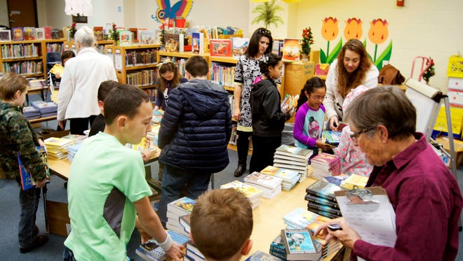 Third-graders choose their own books at Jose Barios Elementary School in Silver City on Wednesday. The students received free books from the Literacy Link-Leamos program, which distributed nearly 8,500 books to Grant County children in December.