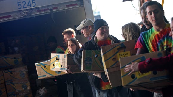 Volunteers and Food Bank employees help unload food donated by Giant supermarket at the Food Bank of Delaware. Two truck loads totaling more than 60,000 pounds of food was donated to the food bank.