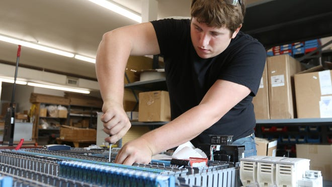 Brandon Kronstedt, a process controls technician with ESE Inc., works in their engineering room May 24, 2016.