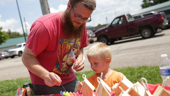 Spencer Shephard and his son, Bo, 3, work on a craft project during the Relay for Life event at the Richland County Fairgrounds last year.