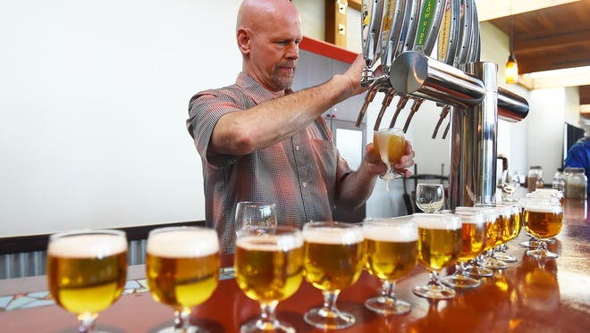 Dave Ponceby pours Blue Paddle samples for a tour group at New Belgium Brewing Company on Friday, February 12, 2016.  Paunchy said the craft brewery expects to sell 1 million barrels of beer this year, it's 25th year in business.