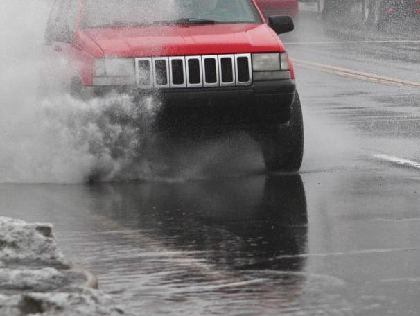 Motorists drive through flooding streets on Maryland Avenue near Germay Drive in Wilmington from melting snow and warm rains passing through the area Wednesday.