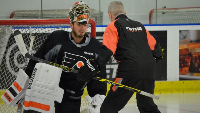 Goalie Michal Neuvirth, left, worked with goalie coach Kim Dillabaugh Monday.