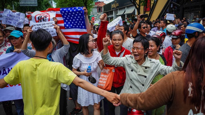 Demonstrators in Ho Chi Minh City protest a draft law that would allow foreign companies 99-year concessions in planned special economic zones, which some view as sweetheart deals for Chinese companies. Among those arrested was an American graduate student, Will Nguyen. He remains in custody.