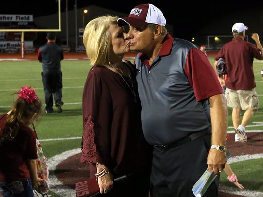 Anita Danaher (left) kisses her husband Phil Danaher on the cheek after defeating Ray High School on Friday, Oct. 14, 2016, at Wildcat Stadium in Corpus Christi.