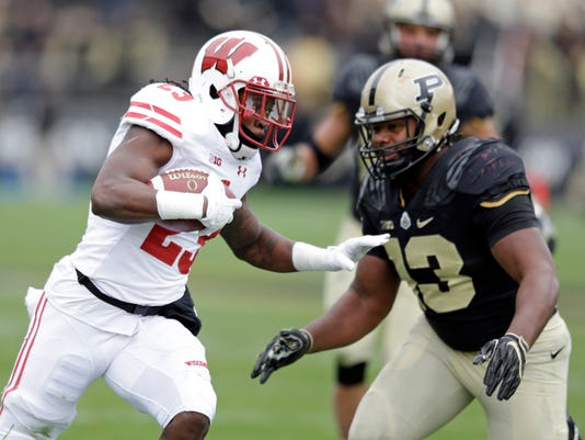 Wisconsin running back Dare Ogunbowale (23) tries to get past Purdue defensive end Gelen Robinson (13) during the first half of an NCAA college football game in West Lafayette, Ind., Saturday, Nov. 19, 2016. (AP Photo/Michael Conroy)