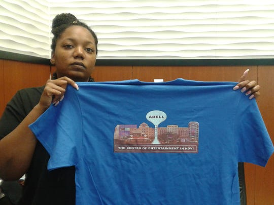 An employee at The Word network shows off  a shirt promoting Kevin Adell's proposed development in Novi. Adell, who owns the network, will give away T-shirts at the next Novi planning commission meeting.