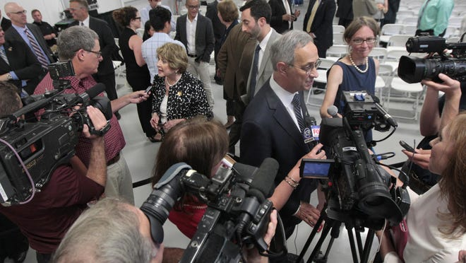 Rep. Louise Slaughter, left, and University president of Rochester Joel Seligman, right, are surrounded by media following the official announcement of the Department of Defense awarding $110 million to help create the new American Institute for Manufacturing (AIM) Photonics in Rochester.