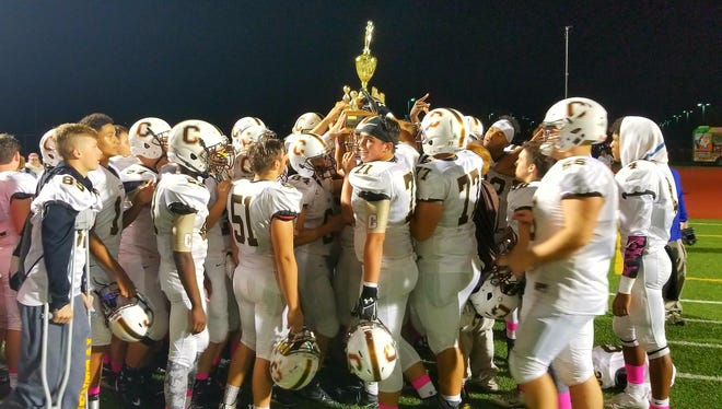 The Central High football team hoists the North Bowl trophy for the third straight year after beating rival North, 60-14, on Friday night at Bundrant Stadium.
