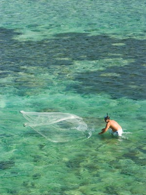 A man is seen net fishing in the waters of Pago Bay.