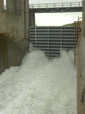 Water gushes out of a partly open spillway gate at the Fort Peck Dam in June 2011.
