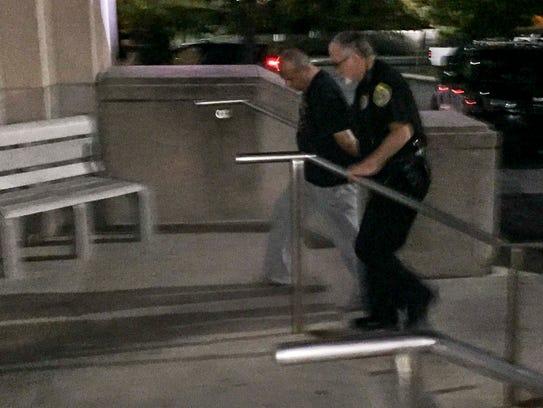 A city police officer leads Deputy Jerry Parks into