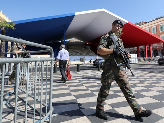 A soldier patrols as workers set up a tribune in the