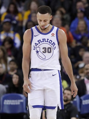 Golden State Warriors guard Stephen Curry walks on the floor during the second half of the team's game against the Atlanta Hawks.
